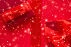 Winter holiday gifts and glowing snow on red background, Christmas presents surprise. New Years Eve celebration, wrapped luxury boxes and Valentines Day card stock photography