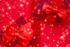 Winter holiday gifts and glowing snow on red background, Christmas presents surprise. New Years Eve celebration, wrapped luxury boxes and Valentines Day card royalty free stock photography