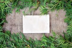 Winter holiday invitation. Pine leaves around the edges of rustic burlap and old paper Royalty Free Stock Images