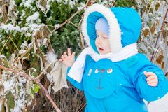 Happy baby boy is glad to snow. Winter holiday outing for children Royalty Free Stock Image