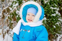 Happy baby boy is glad to snow. Winter holiday outing for children Stock Photography