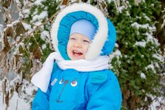 Happy baby boy is glad to snow. Winter holiday outing for children Stock Image