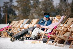 Winter holiday, ski, travel - couple relaxing together in sun at. Winter holiday, ski, travel – smiling couple relaxing together in sun at mountains Stock Photos