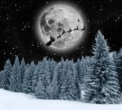 Winter Holiday Theme background. Magic Winter holiday theme with snowflakes, pine forest and silhouette of Santa Claus on the moon Royalty Free Stock Photo