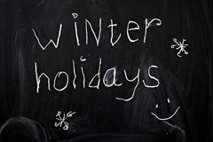 Winter holidays. Inscription winter holidays, written by a child's hand on the chalk board Royalty Free Stock Photography