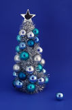 Winter Holidays. Christmas tree with ornaments and a little ball ornament at front Royalty Free Stock Image