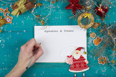 Winter holidays background. Aspirations and dreams is written on a piece of paper by a left-handed woman stock images