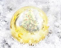 Golden christmas ball with pine tree reflection and snowflakes p Stock Photos
