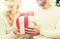 Close up of couple with christmas gift at home. Winter, holidays, christmas and people concept - close up of happy couple with christmas gift at home Stock Photography