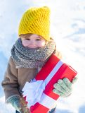 Winter holidays concept. May you have wonderful holiday. Happy winter child hold gift bow snow background. Cute boy in. Winter clothes hat and scarf close up stock photo