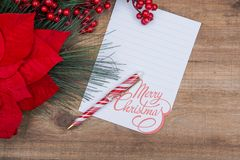 Winter Holidays decoration red poinsettia, pine and berry bush with white Merry Christmas note and red and white striped pen royalty free stock images