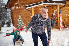 Winter holidays and family concept - happy family with child on. Sled in winter outdoor stock image