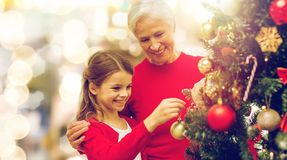 Grandmother and granddaughter at christmas tree Stock Photos