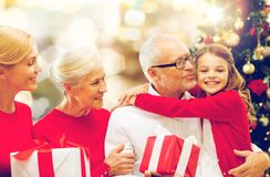 Happy family with christmas gifts over lights royalty free stock photography