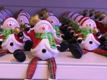 Winter holidays figures. Rows of winter holiday figures of snowmen in Santa Claus coat made of ceramics, close-up on the shelf in a shop Royalty Free Stock Image