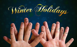 Winter holidays finger group with smiley faces on green backgrou Royalty Free Stock Images
