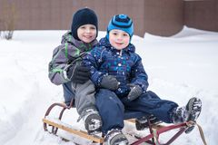 Winter holidays fun. Two boys have together sliding on a pleasan Royalty Free Stock Photo