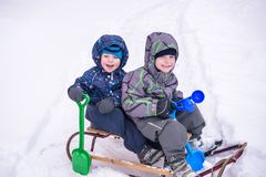 Winter holidays fun. Two boys have together sliding on a pleasan Royalty Free Stock Image