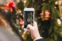 Winter holidays, girl taking picture by phone Royalty Free Stock Photo