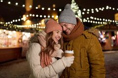 Happy young couple with coffee at christmas market Royalty Free Stock Images