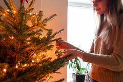 Winter holidays in a house interior. Happy young woman decorating christmas tree at home. Golden and white Christmas. Happy young woman decorating christmas tree royalty free stock image
