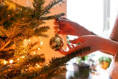 Winter holidays in a house interior. Happy young woman decorating christmas tree at home. Golden and white Christmas. Happy young woman decorating christmas tree royalty free stock photo