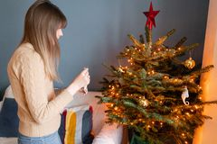 Winter holidays in a house interior. Happy young woman decorating christmas tree at home. Golden and white Christmas. Happy young woman decorating christmas tree stock photo