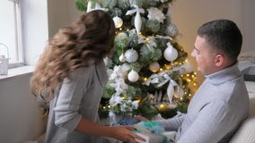 Winter holidays, husband and wife give each other New Year`s gifts on background of decorated fir tree. Winter holidays, husband and wife give each other New stock footage