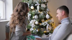 Winter holidays, husband and wife kisses and give each other New Year`s gifts on background of decorated fir tree. Winter holidays, husband and wife kisses and stock footage