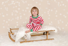 Winter Holidays: Laughing Happy Child in Christmas Pajamas Sled. Winter or Christmas Holidays: laughing, smiling, happy child, kid in red and green striped pj Royalty Free Stock Image