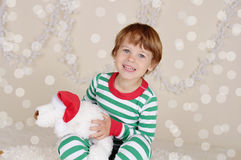 Winter Holidays: Laughing Happy Child in Christmas Pajamas Sled Stock Images