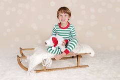 Winter Holidays: Laughing Happy Child in Christmas Pajamas Sled Royalty Free Stock Photography