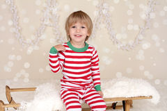 Winter Holidays: Laughing Happy Child in Christmas Pajamas Sled. Winter or Christmas Holidays: laughing, smiling, happy child, kid in red and green striped pj Royalty Free Stock Photo