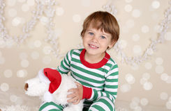 Winter Holidays: Laughing Happy Child in Christmas Pajamas Sled. Winter or Christmas Holidays: laughing, smiling, happy child, kid in red and green striped pj Royalty Free Stock Photos