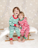 Winter Holidays: Laughing Happy Kids in Christmas Pajamas Sled i. Winter or Christmas Holidays: laughing, smiling, happy kids in red and green striped pj pajamas Stock Images