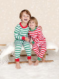 Winter Holidays: Laughing Happy Kids in Christmas Pajamas Sled i. Winter or Christmas Holidays: laughing, smiling, happy kids in red and green striped pj pajamas Stock Photography