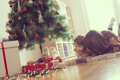 Winter holidays. Mother and daughter lying on a carpet in the living room, next to a nicely decorated christmas tree and enjoying their time together and winter stock photos