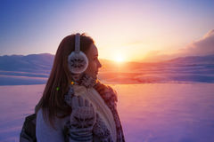 Winter holidays in the mountains. Side view of beautiful girl enjoying amazing view on sunset, spending winter holidays in the snowy mountains, active lifestyle Stock Photos