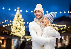 Happy couple hugging over christmas tree lights Royalty Free Stock Images