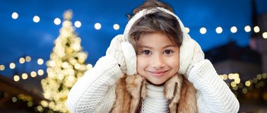Happy girl wearing earmuffs over christmas lights Royalty Free Stock Image