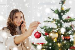 Woman with smartphone decorating christmas tree Royalty Free Stock Images