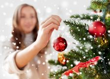 Happy young woman decorating christmas tree Royalty Free Stock Photography