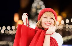 Happy woman with shopping bags over christmas tree. Winter holidays, sale and people concept - smiling young woman in hat and scarf with red shopping bags over royalty free stock photo