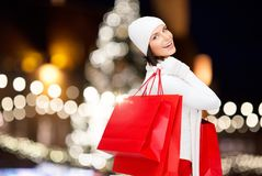 Happy woman with shopping bags over christmas tree Stock Photos