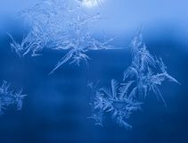 Winter Holidays Season Fantasy World Concept: Macro Image of Natural Ice Crystals Patterns on a Blue Frosted Window Pane With Sun. Glow. Hoarfrost Background royalty free stock photos