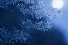 Winter Holidays Season Fantasy World Concept: Macro Image of Natural Ice Crystals Patterns on a Blue Frosted Window Pane With Sun. Glow. Hoarfrost Background royalty free stock photo