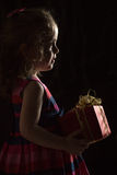 Winter holidays - silhouette of a beautiful little girl with present over black background Royalty Free Stock Photography