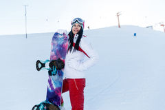 Winter holidays of sports brunette. With snowboard at ski resort Stock Photo