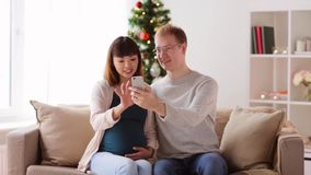 Man and pregnant wife with smartphone at christmas stock video