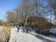Winter in Holland. Giethoorn, Netherlands - February 6, 2012. Ice skaters in Dutch winter landscape Stock Photography